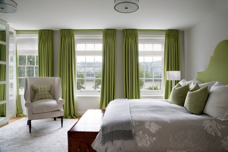 basement bedroom idea dark citrussy green window curtains grey walls grey corner chair with pillow grey bedding treatment traditional bed frame with green headboard