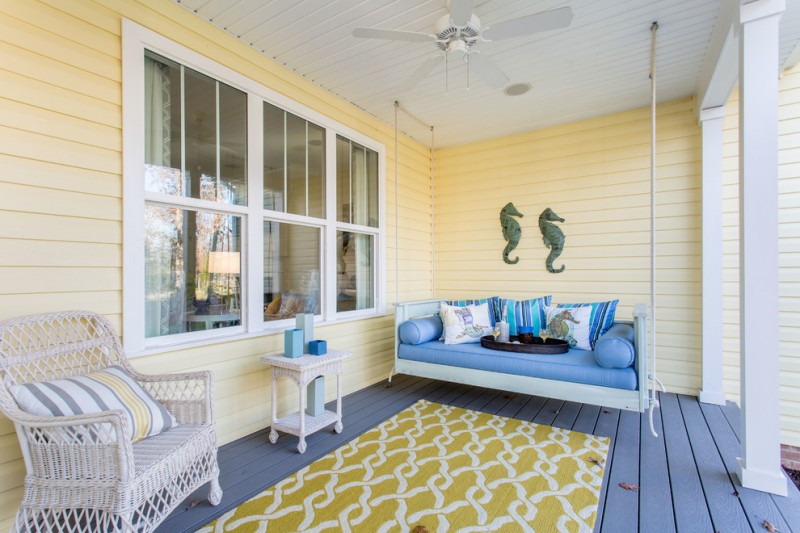beach style front porch hanging swing in blue white chair with strippes throw pillow white side table yellow area rug with white accents blue wood board floors