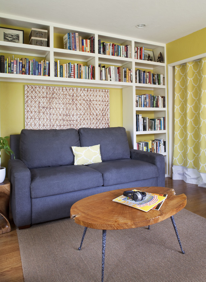 blue sleeper couch idea oval shaped wood top coffee table with blue thin legs yellow walls wall mounted bookshelves in white