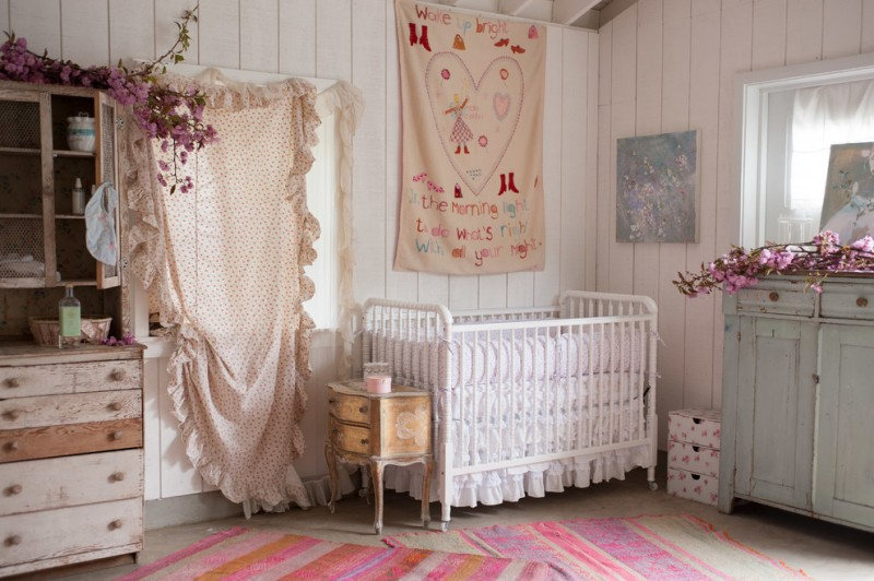 bohemian nursery idea colorful rug vintage style crib in white vintage style side table vintage dressing white wood board walls decorative fabric wall decorations