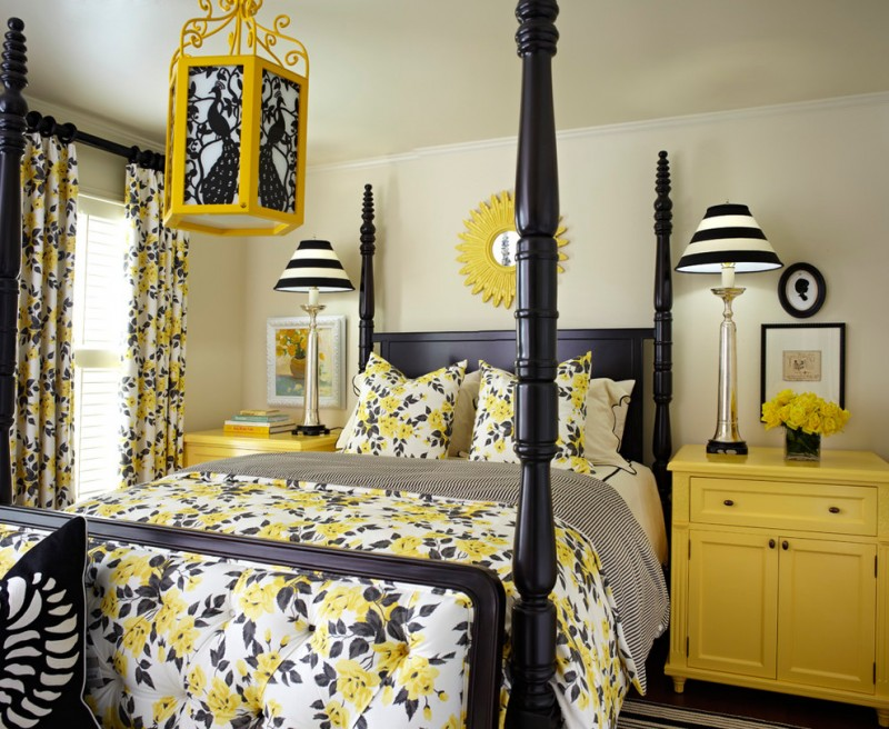 classic style bed frame in black and with canopy black mustard quilt and draperie with floral motifs mustard bedside tables mustard framed mirror on wall mustard black pendant lamp
