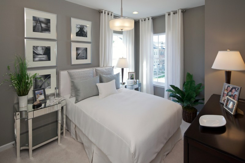 contemporary bedroom in basement white window curtains white bed slipcover grey pillows dark toned wood dressing victorian style bedside tables grey walls