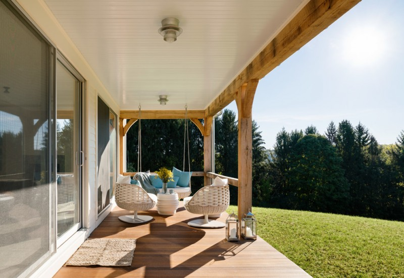 contemporary farmhouse porch idea with exposed beams on ceilings a couple of white lounge chairs wine drum center table in white hanging swing with blue pillows