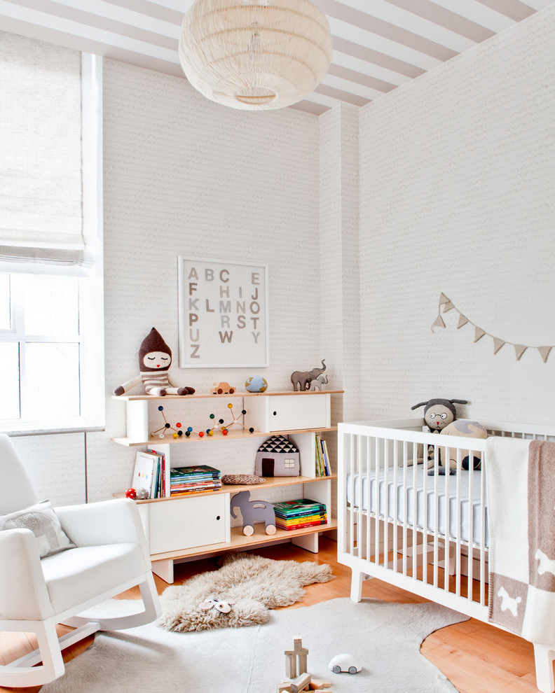 contemporary nursery idea with dominant white white walls medium toned wood floors asymmetric modern rug in soft grey white rocking chair white bookcase with wood color accents modern white crib