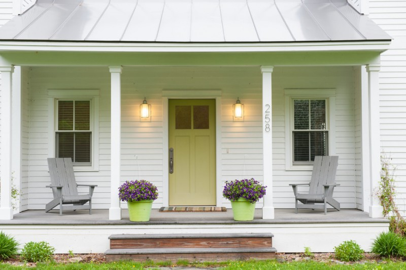 country style front porch white siding exterior walls grey wood chairs green pots with purple flowers a couple of wall lamps