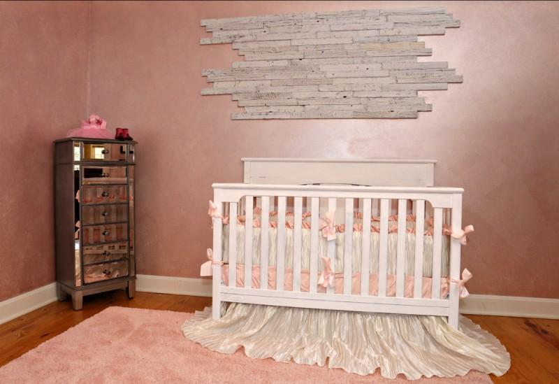 dramatic peach & pink nursery idea white baby crib with silky white skirt baby pink rug dark toned wood floors dark peach walls corner dresser