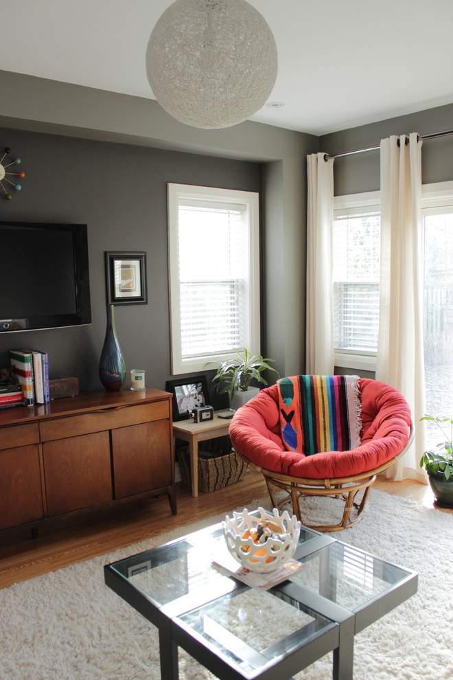 eclectic family room in basement light basement window curtains white window shutters grey walls dark wood TV console white shag rug modern glass top center table red decorative side chair