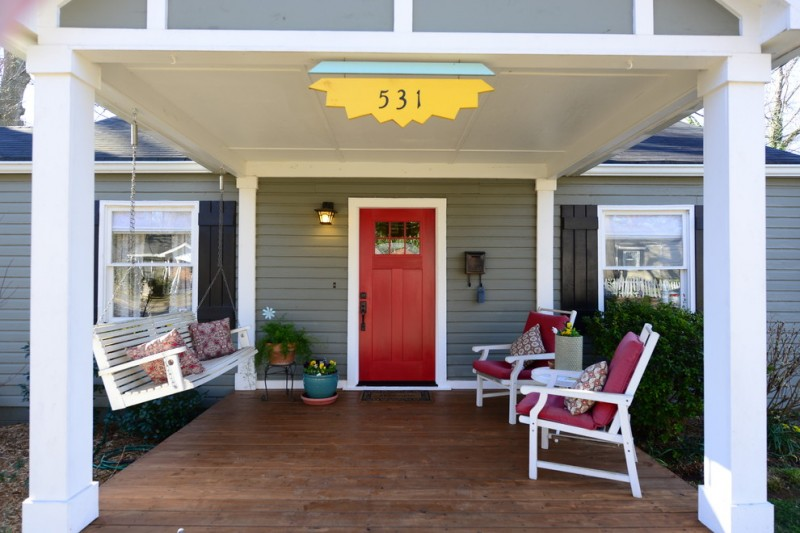 farmhouse style front porch idea grey siding exterior walls velvet front door with white trim wood swing bench in white white chairs with velvet foams