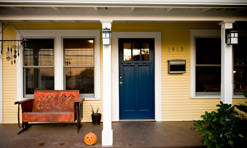 front porch idea navy blue front door yellow siding exterior walls white trimmed exterior windows copper bench with back