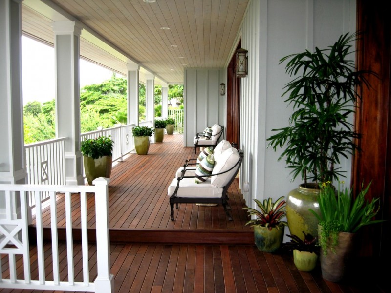 front porch idea white exterior dark wood front door a couple of wall lamps black wrought iron lounge chairs with white covered seating pad dark toned wood board floors white painted railing system