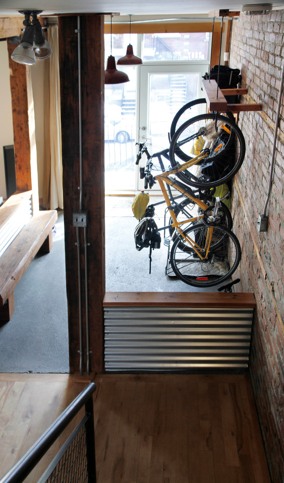 industrial entry way idea wall mounted bike rack with kickstand support red bricks walls concrete floors