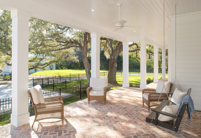 large transitional front porch white roof and pillars rattan chairs with white covered foams dark toned hanging swing with white throw pillows