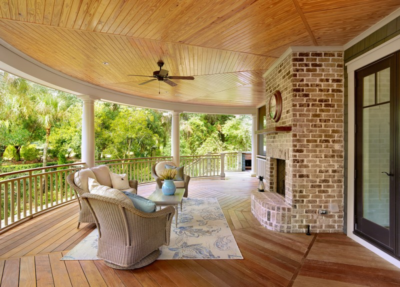 large victorian style porch with curved rails outdoor fireplace with whitewashed red brick surroundings soft toned chairs with comfy pillows white area rug with blue accents