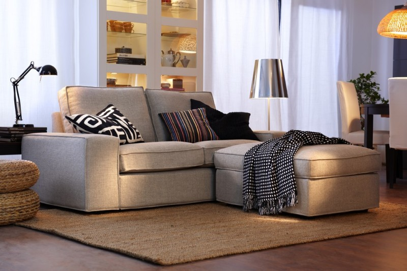 light brown couch with sectional lounge feature and under storage unit multicolored throw pillows juted area rug dark toned wood floors