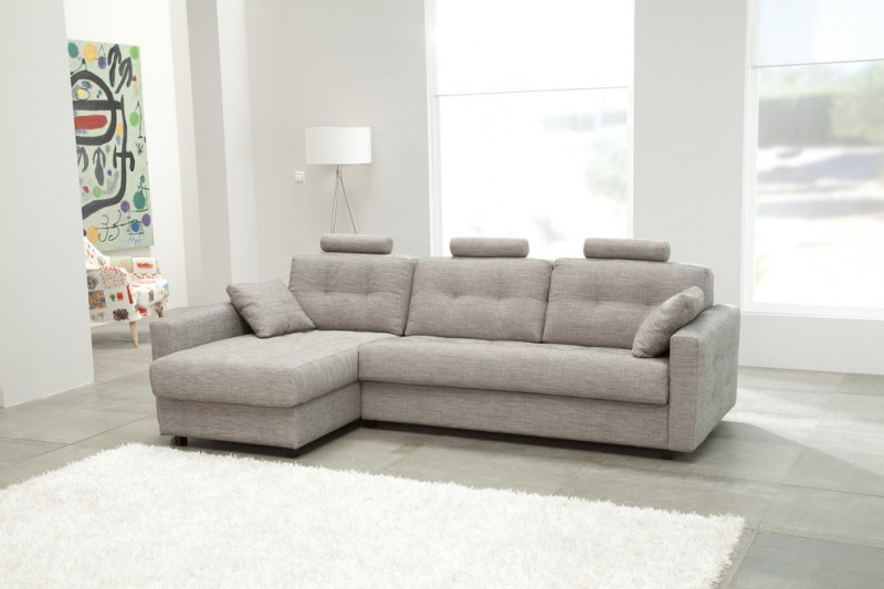 light grey sleeper couch with head rest and under storage feature white shag rug concrete tiles floors light grey walls