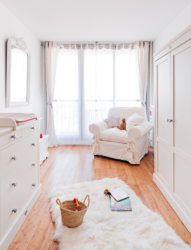 light palettea nursery idea medium toned wood floors white nursery chair slipcover white changing table with drawer system white framed mirror white window curtains