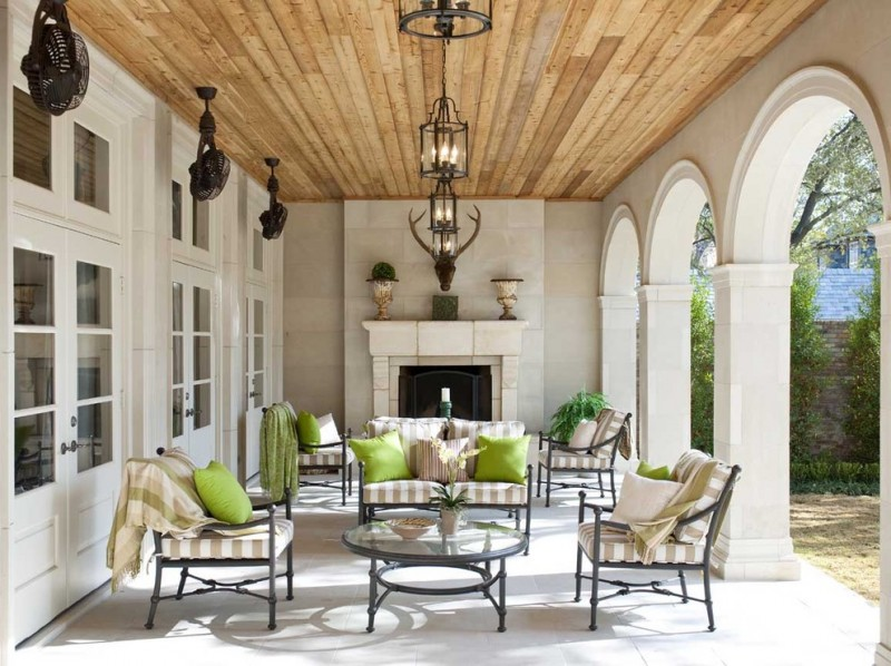 mediterranen front porch with outdoor fireplace with marble surroundings higher exterior glass curved front gates black wrought iron seats with stripped seating pads