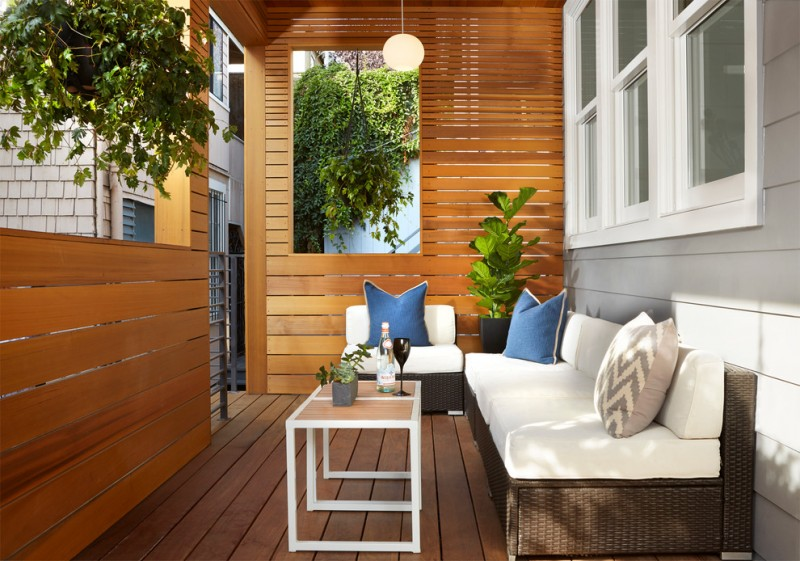 medium size front porch with side yard walls dark couch and chair with white covered foam blue accent pillows modern center table with square shaped wood top and white construction
