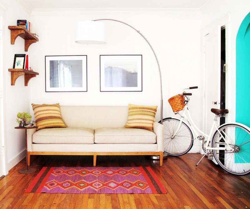 mid century modern sofa in soft cream dark toned wood floors tribal area rug white walls feminine bike decoration large floor lamp