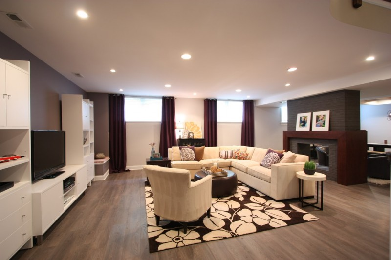 modern basement design dark brown window curtains light grey walls wood floors fireplace with tiles surround L shaped white sectional medium sized area rug with large flower motifs