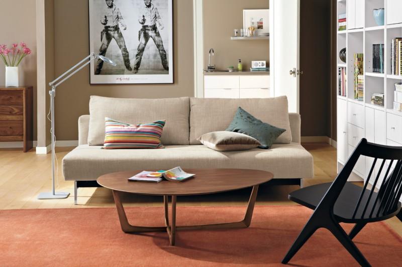 modern minimalist sleeper sofa in soft neutral tone modern minimalist wood coffee table with oval shape top light toned wood floors