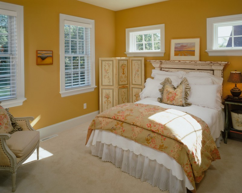 mustard walls white trimmed windows with white shutters white bed slipcover and pillows gold toned comforter with motifs