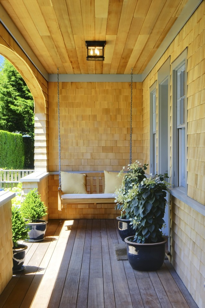 narrow porch design shingles exterior walls pale blue trimmed exterior windows wood porch swing with light yellow accent pillows wood board floors