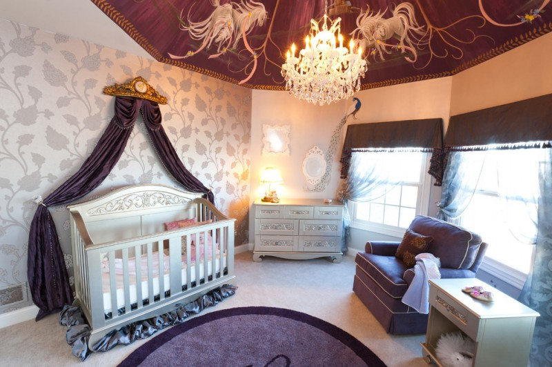 purple decorated nursery round purple rug glossy grey crib with purple silk skirt and canopy light wallpaper accented with silver toned floral motifs purple nursery chair light grey dressing
