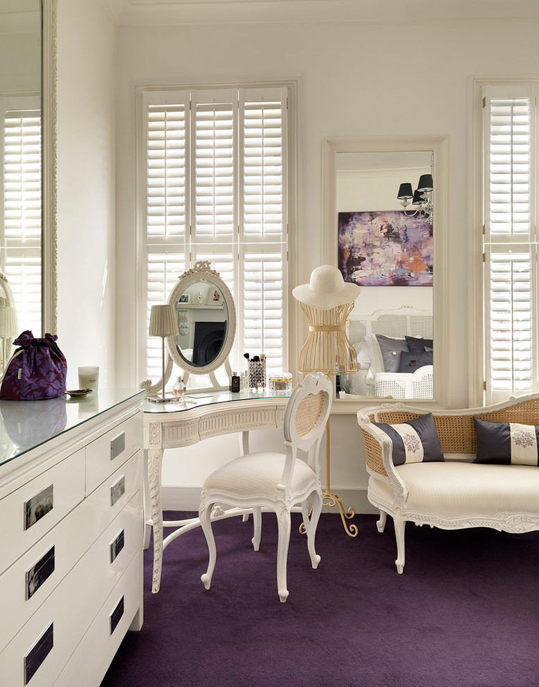 simple French style makeup vanity table in white with round mirror and white vanity chair purple carpet windows with white shutters