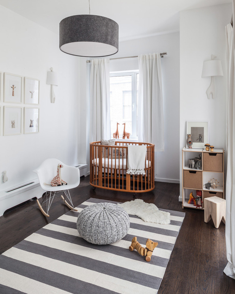 simple modern nursery idea white walls white window curtains medium toned wood crib in round shape mid century modern rocking chair in white stripped rug dark toned wood floors