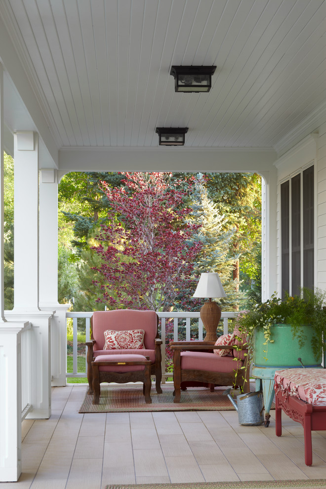 small front porch with whire rails and pillars classic designed porch seats with soft maroon fabrics small sized area rug wood board floors