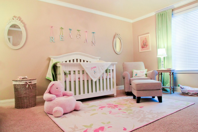 soft colored nursery idea baby pink walls a couple of round shaped decorative mirrors white crib baby pink rug with multicolored butterflies motifs basket for storage green curtain pink nursery chair