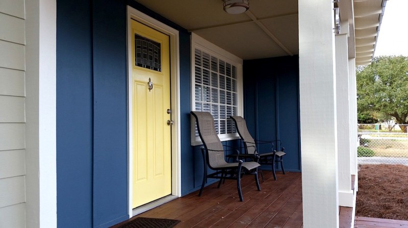 traditional front porch design navy blue exterior walls light yellow front porch with white trim white trimmed exterior window with white shutter black wrought iron chairs