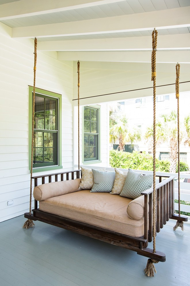 traditional front porch idea white siding exterior walls green trimmed exterior windows hanging settee with soft colored accent pillows and bolsters
