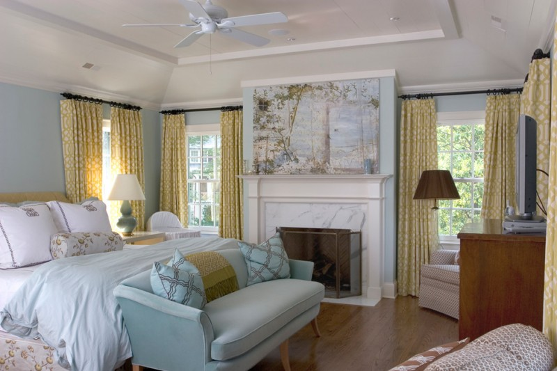 traditional guest room mustard window curtains dark wood floors white bedding treatment light blue loveseat fireplace with marble surroundings