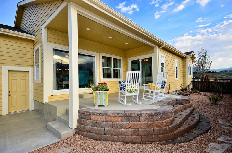 traditional porch design yellow sidinge exterior walls white trimmed exterior windows white rocking chairs with multicolored seating pads colorful plant box