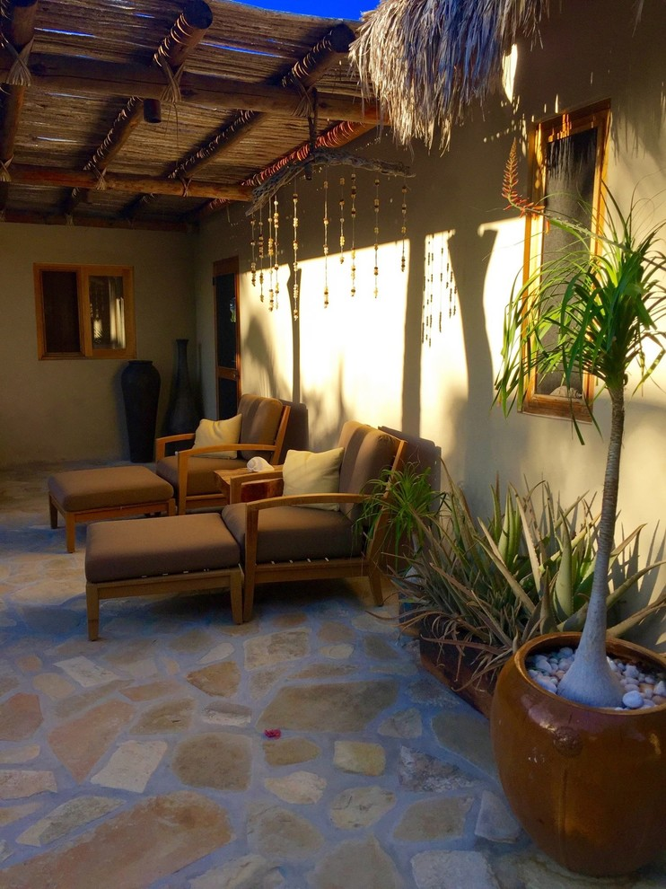 tropical front porch idea concrete paving floors soft chairs with tables gold toned wall painting tropical plants for decorations