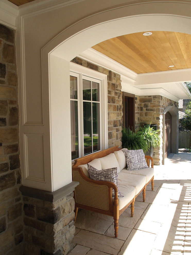 victorian style porch with limestone base wooden bench and natural stone exterior walls