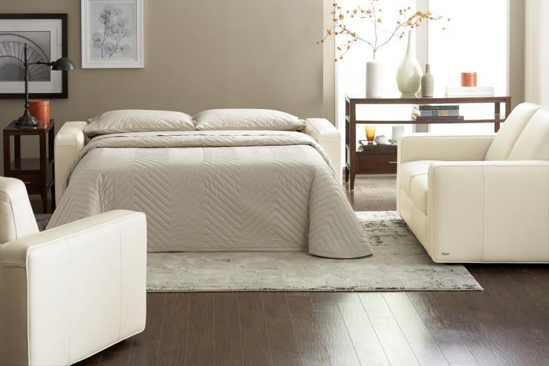 white sleeper sofa white comforter white linens white area rug dark wood floors light grey walls