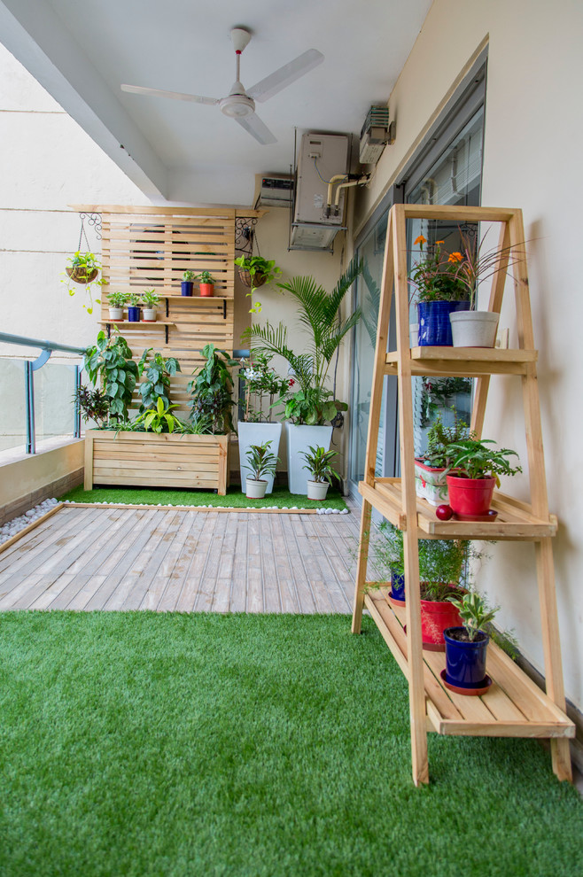 Scandinavian balcony idea synthetic green grass floors wood boards floors wood shelves for planters colorful planters