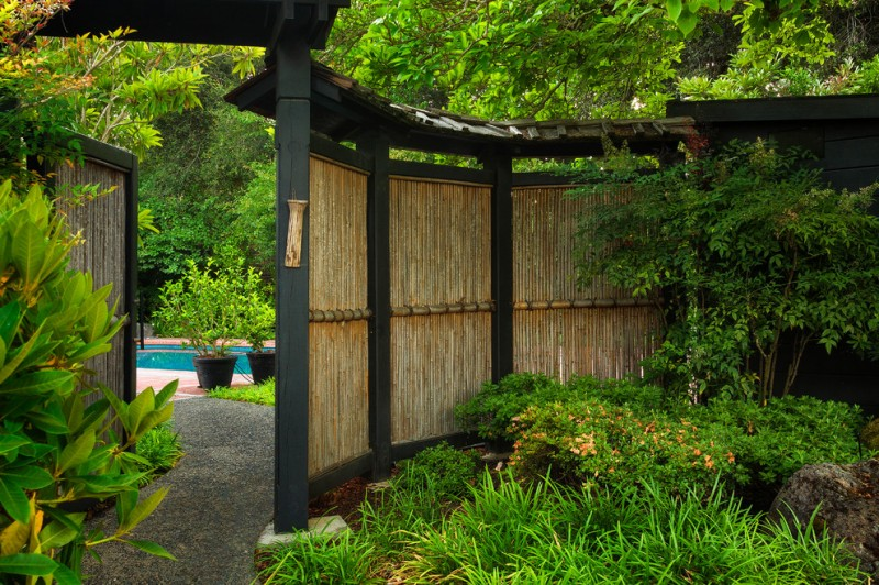 asian style landscape idea bamboos fence idea with dark painted fence posts and clay burnt roofs