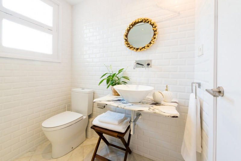 clean line scandinavian bathroom vanity marble 'board' countertop white vessel bowl sink x base wood chair white toilet white subway ceramic tiles walls round mirror with gold toned frame
