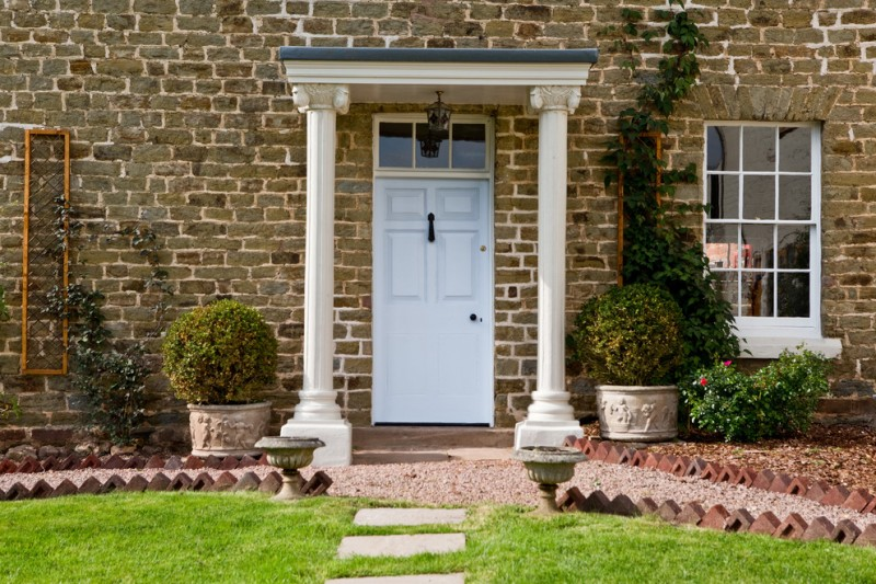 colonial front door in white with transom Victorian style entry gate old and shabby brick exterior walls frameless exterior glass window