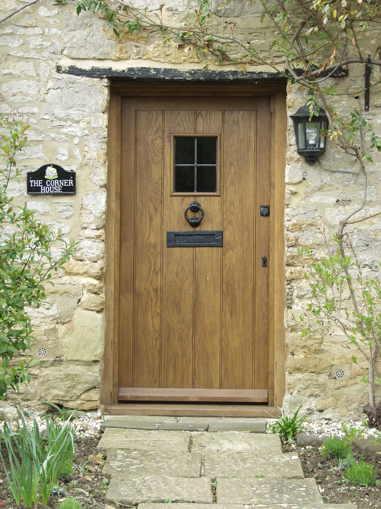 colonial rustic front door idea with centered and small window accent hard textured stone exterior walls traditional exterior wall lamp