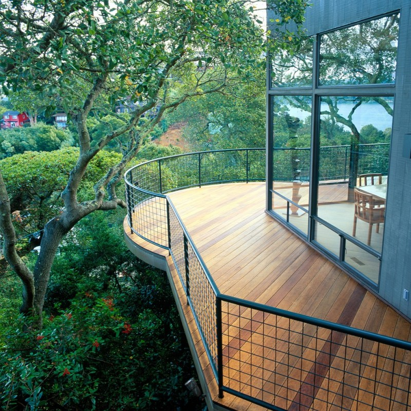 contemporary balcony with angled wood decking and black stined wire rails