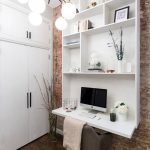 Contemporary Home Office Idea Large Built In Working Desk In White Integrated With Shelves Red Bricks Walls Dark Toned Hardwood Floors