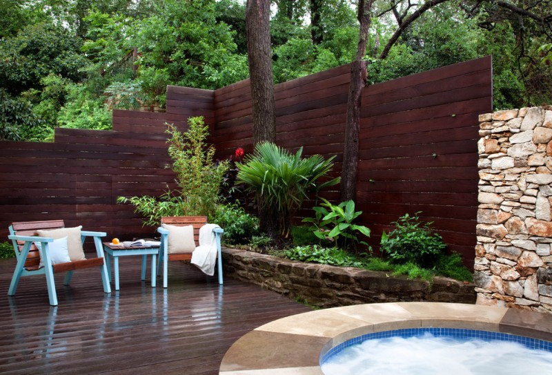 contemporary patio with decking wood patio furniture with blue accent dark toned wood fencing idea in contemporary style stone planting beds