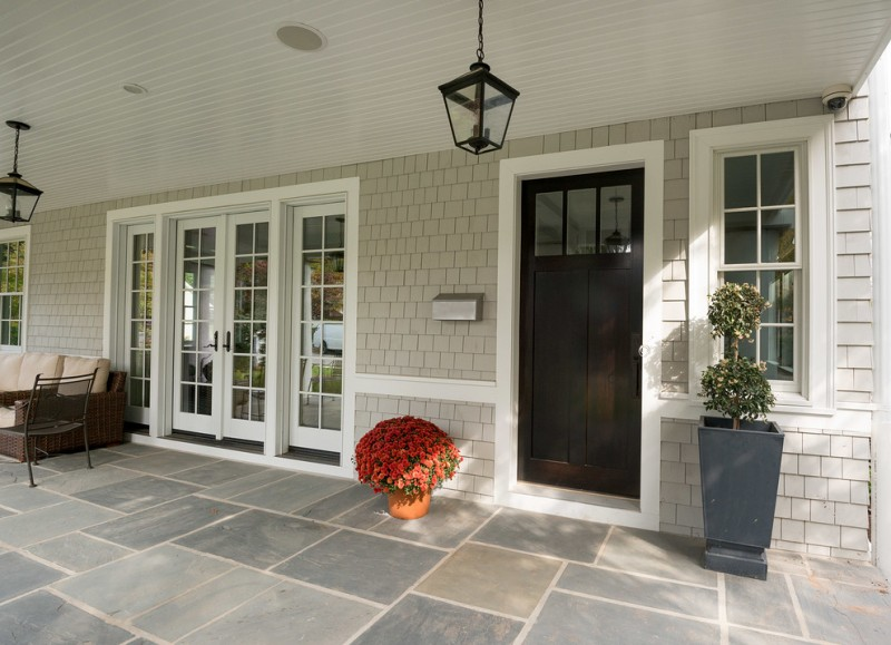 dark colonial front door with upper window accents and white door trims light grey wood shingles concrete paving floors traditional exterior pendant lamps