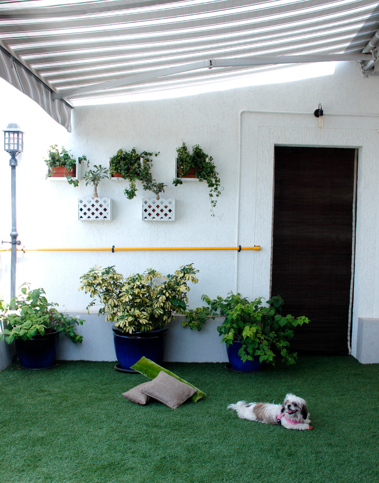 eclectic balcony idea synthetic green grass carpeting dark blue planters decorative wall mounted planters in white white shelves for planters