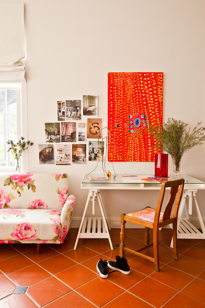 eclectic home office idea bright orange wall board organizer glass top working desk in white wood working chair sofa with flower motifs terracotta tiles floors